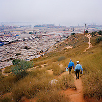 Two men walk down a track that leads from Alto Mar, a wealthy district of Luanda, towards a slum area adjacent to the port.