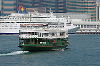 "The Star Ferry Company's ""Golden Star"" (built 1989) crossing Hong Kong's Victoria Harbour, passing Star Cruises' ""Star Pisces"" docked at Ocean Terminal in Tsim Sha Tsui"