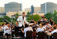 "Event photography of the Charlotte Symphony performing in a free outdoor concert June 17, 2012 at Duke Energy's McGuire Nuclear Station EnergyExplorium in Cornelius, NC. The symphony orchestra performed a ""musical travels"" program. Jacomo Rafael Bairos conducted."