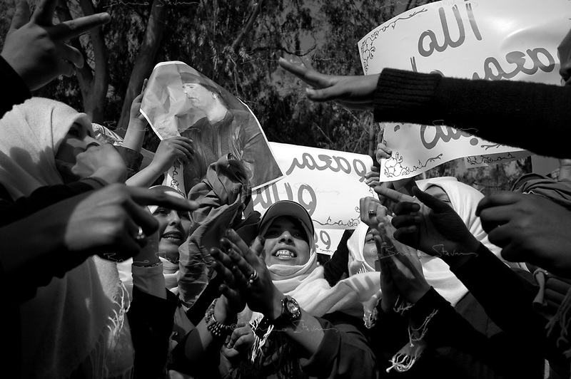 Tripoli, Libya, March 12, 2011.Government officials hand out Khaddafi posters and flags to school children brought from their schoo across the street to stage a pro-Khaddafi demonstration in front of a hotel housing foreign journalists by their teachers.