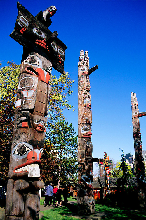 Collection of dramatic, old Totem Poles in Thunderbird Park, downtown Victoria, BC.
