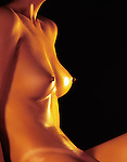 Beautiful naked suntanned shiny woman's body closeup of bare breasts on black background