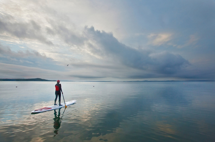 A woman paddles on a stand-up paddleboard in Frenchman Bay near Bar Harbor, Maine, USA