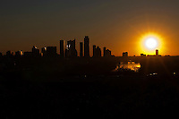 Austin Skyline silhouette at sunrise with a bright yellow sun rising above the downtown city skyline stock photo.