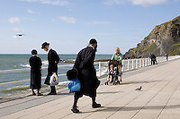 An Hasidic family walk along the promenade by the beach in Aberystwyth.