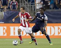 Chivas USA midfielder Nick LaBrocca (10) starts forward as New England Revolution midfielder Shalrie Joseph (21) reacts. In a Major League Soccer (MLS) match, Chivas USA defeated the New England Revolution, 3-2, at Gillette Stadium on August 6, 2011.