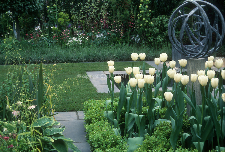 Spring garden scene with sundial, white tulip bulbs, plants, lawn, patio, garden border