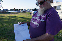 John Watson holds notice from San Leandro City to remove plants and decorations from city property; the closed observation deck at the San Leandro Marina.