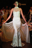 Model walks the runway in a Riche wedding dress - low back silk taffeta gown with tulle overlay and beaded lace at neck, by Sarah Jassir, for the Sarah Jassir Couture Bridal Fall 2012 Opulence collection.