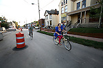 Bike Prom participants ride through the Limestone Street to stop by Zag's Boutique and Art Gallery and The Soundbar Saturday evening. Photo by Adam Wolffbrandt | Staff.