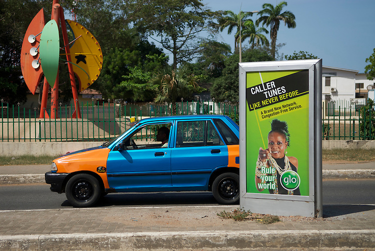 An orange taxi passes a green advert for Glo, a mobile network about to lauch in Ghana, May 2010, Liberia Road, Accra. Caller Tunes change the ringing tone people hear when they ring you. In August 2009 Vice President John Dramani Mahama spoke about the possibility of the  National Communications Authority (NCA),applying sanctions  to mobile operators where networks had become congested. Claims about network reliability became common marketing messages.
