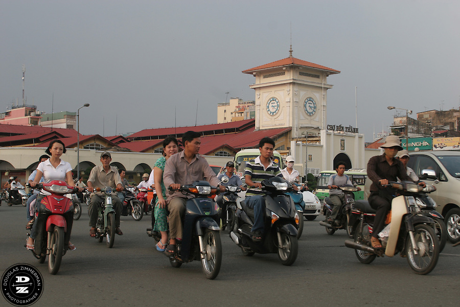 Motorbikes pass in front of Ben Thanh Market in Ho Chi Minh City, Vietnam.  Ben Thanh is a huge indoor market selling a large variety of goods.  Photograph by Douglas ZImmerman