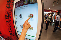 """Diners order at a """"Create Your Taste"""" kiosk at a McDonald's in New York on Tuesday, August 4, 2015. The interactive iPad-like digital displays allow customers to customize their order with toppings, new sauces, etc. and have them delivered to their table in a few minutes. McDonald's, which has seen same-store sales drop over three years, is using the kiosks to compete with fast casual restaurants such as Chipotle, Fatburger and a host of others. (© Richard B. Levine)"""
