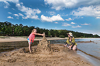 Kid and mother building sandcastle. Kauksi beach, lake Peipsi in Estonia.