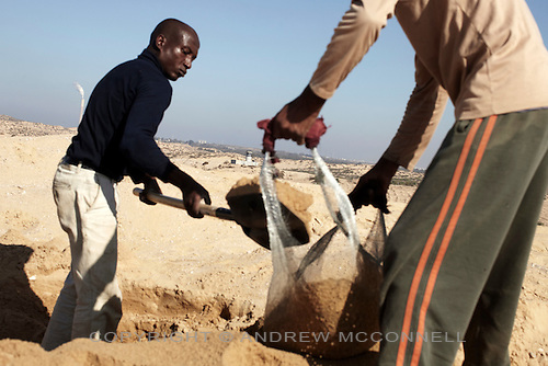Men sieve sand for gravel in clear view of an Israeli watch tower at Gaza's northern border. Under the blockade there is a severe lack of building materials and many Palestinians risk their lives to collect these materials in the buffer zone that surrounds Gaza.