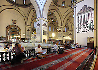 Prayer hall of the Grand Mosque or Ulu Cami, built 1396-99 under the Ottoman Sultan Bayezid I by the architect Ali Neccar in the Seljuk style, Bursa, Turkey. Here we see some of the 192 monumental wall inscriptions written by the famous calligraphers of that period and the fountain (sadirvan) where worshipers can perform ritual ablutions before prayer. The mosque is a large rectangular building with 2 minarets, and 20 domes supported by 12 columns. Supposedly the 20 domes were built instead of the 20 separate mosques which Sultan Bayezid I had promised for winning the Battle of Nicopolis in 1396. The dome over the sadirvan is capped by a skylight creating a soft light which illuminates the large building. The mosque is in the old city centre of Bursa and remains the largest mosque in the city. Picture by Manuel Cohen