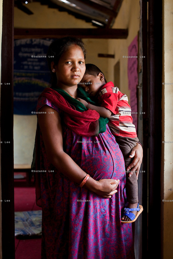Manisha Sunar, 18, carries her 2 year old son, as she poses for a portrait at the information center near her home in Lekhapharsa vilage, Surkhet district, Western Nepal, on 30th June 2012. Manisha was married off when she was 14 but secretly used contraceptives with the help of her husband's sister. When he found out, he forced her to stop and she was soon pregnant with no money to terminate it. She's now 8 months pregnant again even though her husband neglects and abuses her and her son. In Surkhet, StC partners with Safer Society, a local NGO which advocates for child rights and against child marriage. Photo by Suzanne Lee for Save The Children UK