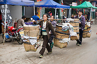 People carry baskets to market day in Baisha, near Guilin, China