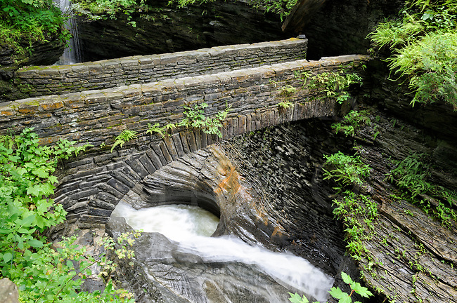 Stone bridge over rushing whitewater in rocky gorge at Watkins Glen State Park, New York, USA.