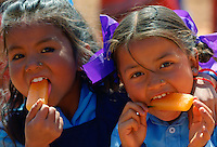 Nepalese girls (possibly sisters) enjoying orange ice lollies in rural Nepal.