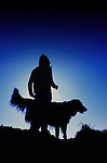 A young girls silhouette standing with her dog