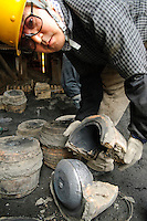 """Opening a cast containing an iron kettle, Oigen """"Nambu Tekki"""" ironware foundry, Esashi, Iwate Prefecture, Japan, August 28 2008."""