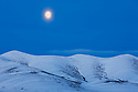 Canada, Yukon; Full moon rising above snow-covered Richardson Mountains at the beginning of winter, at the Arctic Circle, tundra