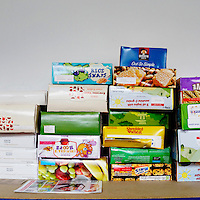 Cereal boxes lie stacked on a shelf at the Camden food bank in north London. Volunteers meet customers, offering a hot drink and cake before an interview is carried out to assess the person's need. After this specially-selected bags of food are made up.Many food banks are run in or by local churches though not all volunteers at this bank would describe themselves as regular church goers.<br /> <br /> I