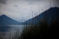 A fisherman on Lake Atitlán, Guatemala among reeds and volcanoes, seen from San Marcos la Laguna.