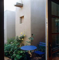 Bright colours sing against the greyish-brown adobe surface of this contemporary house near Santa Fe, New Mexico