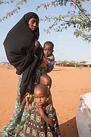 Kenya - Dadaab - A mother queues for food distribution at Ifo camp with her three children.