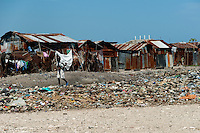 Haitian boy walks in front of shacks in the slum of Cité Soleil, Port-au-Prince, Haiti, 11 July 2008. Cité Soleil is considered one of the worst slums in the Americas, most of its 300.000 residents live in extreme poverty. Children and single mothers predominate in the population. Social and living conditions in the slum are a human tragedy. There is no running water, no sewers and no electricity. Public services virtually do not exist - there are no stores, no hospitals or schools, no urban infrastructure. In spite of this fact, a rent must be payed even in all shacks made from rusty metal sheets. Infectious diseases are widely spread as garbage disposal does not exist in Cité Soleil. Violence is common, armed gangs operate throughout the slum.