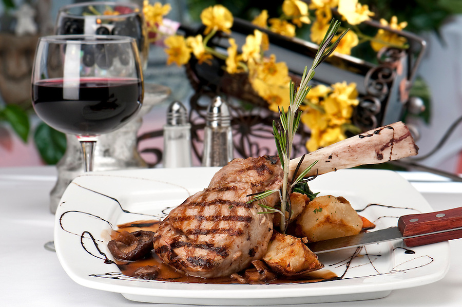Broiled center cut veal chop with sauteed onions and mushrooms and table setting with wine,