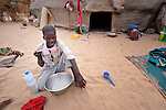 A boy eats outside his family's tent in Timbuktu, a city in northern Mali which was seized by Islamist fighters in 2012 and then liberated by French and Malian soldiers in early 2013. This boy belongs to the Bella ethnic group, which has traditionally been exploited by Timbuktu's lighter-skinned groups.