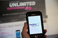 A consumers uses her MetroPCS phone while browsing the T-Mobile USA website in New Yorn on Thursday, October 11, 2012. MetroPCS and T-Mobile USA recently announced that  Deutsche Telekom AG, the owner of T-Mobile USA will now hold a 74 percent stake in the merged companies with the remaining shares held by MetroPCS shareholders who will also get a $1.5 billion payment. The combined companies will have almost 42 million subscribers but will still only be the fourth largest US cell phone company. (© Richard B. Levine)