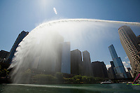 A sprinkler shoots water over the Chicago River while I kayak upriver.