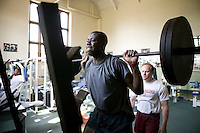 Athletic trainer Al Wood (R) watches English teenager Eric Boateng exercise in the gym at St Andrews High School in Middletown, DE, United States, 19 April 2005.