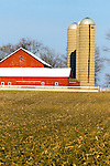 Twin silos stand tall over a vintage red bar on a small farm in rural Illinois.