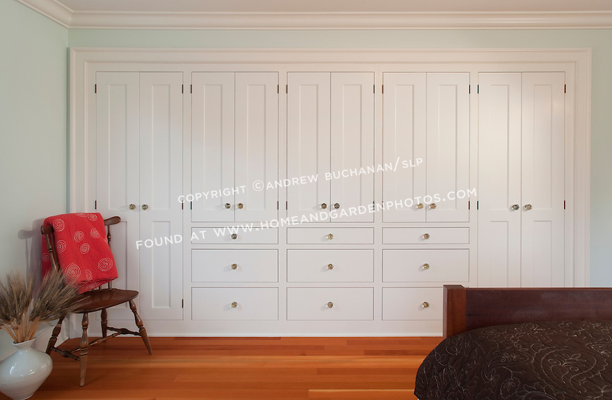 A solid wall of built-in storage cabinets and warm fir floors in the second floor guest bedroom of a new contemporary home built in a cleanly-styled, traditional Shaker style.  A red, quilted comforter, a high-back, Shaker style chair, and a floor vase of dried wheat complete this quiet, ordered scene.  The homeowner is a cabinetmaker with a Master's degree in art who designed the house and crafted all of the cabinetry, built-ins, and most other woodwork himself.