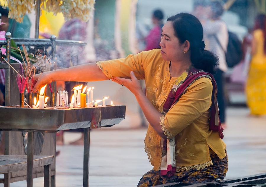 YANGON, MYANMAR - CIRCA DECEMBER 2013: Woman lighting incense in the Shwedagon Pagoda, a famous landmark in Yangon