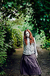 A girl standing on a road framed in ivy.