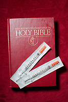 "Sterile syringes and a Bible on a pew at Green Street Church in Winston-Salem, NC, which houses The Twin City Harm Reduction Collective, a needle exchange for addicts. Colin Miller, a recovering addict and one of the collective's founders, cites Jesus' words in Matthew 25:40 as a motivation to help addicts use drugs in a less harmful way, and ultimately become sober: ""Truly, I say to you, as you did it to one of the least of these my brothers, you did it to me.""  (Justin Cook)"