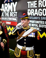 A soldier wears traditional army dress in front of an army recruitment advertisement at the Inveraray Highland Games, held at Inveraray Castle in Argyll.