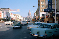 In this historical 1965 photo, antique automobiles fill Congress Avenue leading up to the Texas State Capitol. Retail stores line the streets all the way up to the Texas State Capitol. These stores include Zales Jewlery, Baker's Shoes, Kress and Krugers Jewelers - Stock Image.
