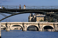 People crossing the Pont des Arts bridge over the Seine with the Pont Neuf in the background, Paris, France.