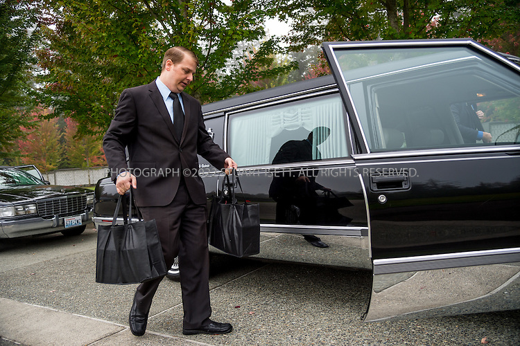 9/30/2016-- Tahoma National Cemetery, Kent, WA, USA<br /> <br /> Here: After arriving at the Tahoma National Cemetery, undertaker James Lindley transfers 2 bags containing the remains of 4 veterans into a hearse for their final placement at the cemetery.<br /> <br /> James Lindley, 34, an undertaker and US Marine Corp Veteran, works at the Columbia Funeral Home in Seattle, Washington and has taken it upon himself to process the remains of indigent veterans and ensure their remains are placed in Tahoma National Cemetery in nearby Kent, WASH. The veterans are given full military funerals with active service members as well as volunteers who stand-in for unavailable next-of-kin, accepting the folded flags provided by the Veterans Administration.<br /> <br /> On this day, with the help of Mr. Lindley, the remains of 4 veterans were interred at the Tahoma National Cemetery: <br /> <br /> Richard Fesler, born 1951, died2014. US Army Veteran<br /> Rocky Stallone, born 1951, died 2014. Marine Corps veteran<br /> Russell Ristow, born 1944, died 2014. US Army veteran.<br /> Wayne Roberts, Born 1937, died 2014. US Navy veteran.<br /> <br /> <br /> Credit: Stuart Isett for The Wall Street Journal. <br /> VETBODIES<br /> <br /> &copy;2016 Stuart Isett. All rights reserved.
