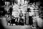 Workers in front of bags of rice at a village rice mill outside Bago, Burma.