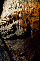 STALACTITES &amp; STALAGMITES IN LIMESTONE CAVERN<br /> Calcium Carbonate Deposits- Big Room Flowstone<br /> Stalactites hang from the top of limestone caverns, formed by the dripping of mineralized solutions. Corresponding columnar deposits, Stalagmites, are built upward. Carlsbad.