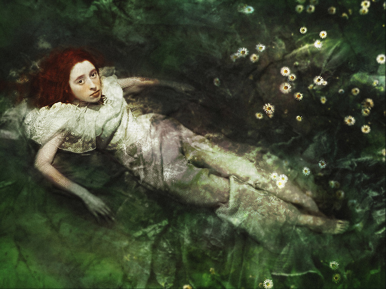 A woman with red hair and sad facial expression, dressed in a white floral skirt, drowning in a water full of camomiles.