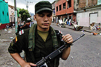 A young Colombian policeman guards the entrance to the slum of Calvario, Cali, Colombia, 4 April 2004. Calvario, a slum right in the centre of the city, is considered the social bottom of Cali society. Poor dwellers recollect the garbage in the near city centre to sell it for recycling, while their children get high by sniffing the shoe glue on the dirty streets of ghetto. The order in Calvario is maintained by the illegal authorities, usually former policemen or army members, who set their own rules. Criminality, drug abuse, unemployment never allow the slum people jump off the misery and stop being the second category citizen within the rigid society of Colombia. Although Christian missionary organizations attempt to provide help, the overall situation does not improve.